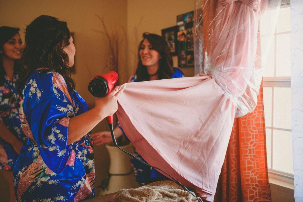 Bridesmaids blow drying a bridesmaid's dress that got wet. They are wearing blue robes and laughing with each other.