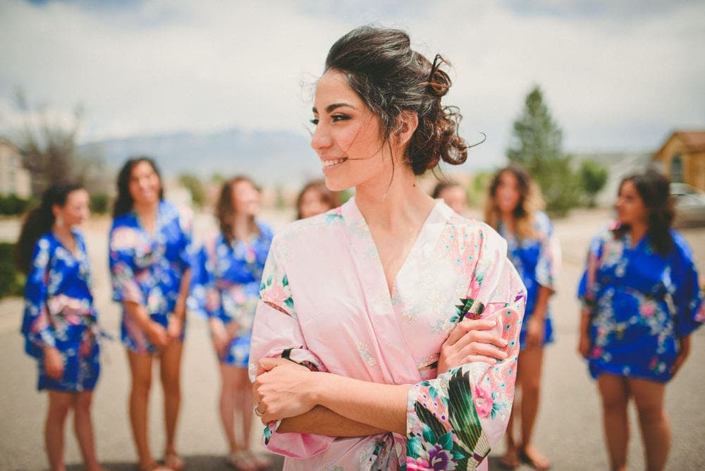 New Mexico bride wearing a pink robe standing in the foreground smiling with her arms crossed. Her bridesmaids are standing behind her.
