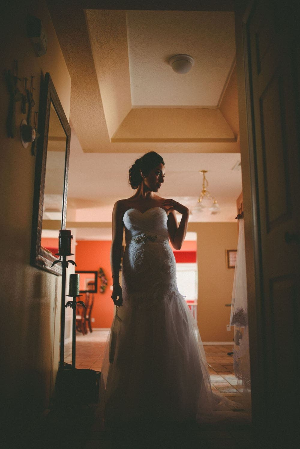 New Mexico bride elegantly silhouetted as she wears her wedding dress for the first time. She's looking to her left and touching her left shoulder with her left hand.
