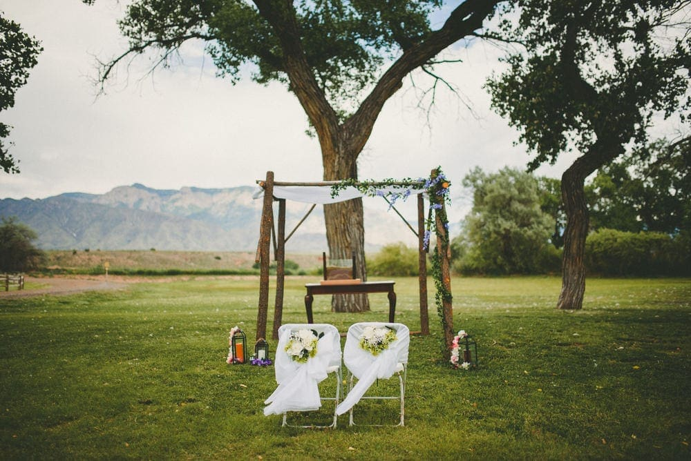 The wedding ceremony arch at Sandia Lakes Park. Tall trees stand behind the arch. The Sandia Mountains can be seen in the background.