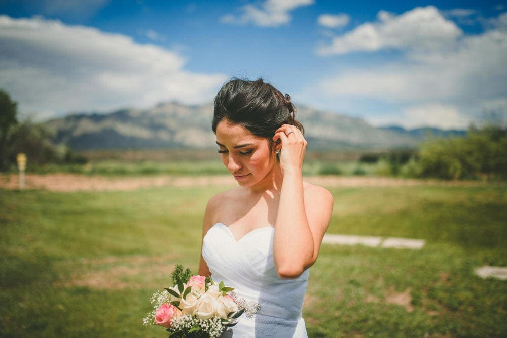 The bride looking down at her bouquet and lifting her hair over her left ear with her left hand. The Sandia Mountains and blue sky is shown in the background.