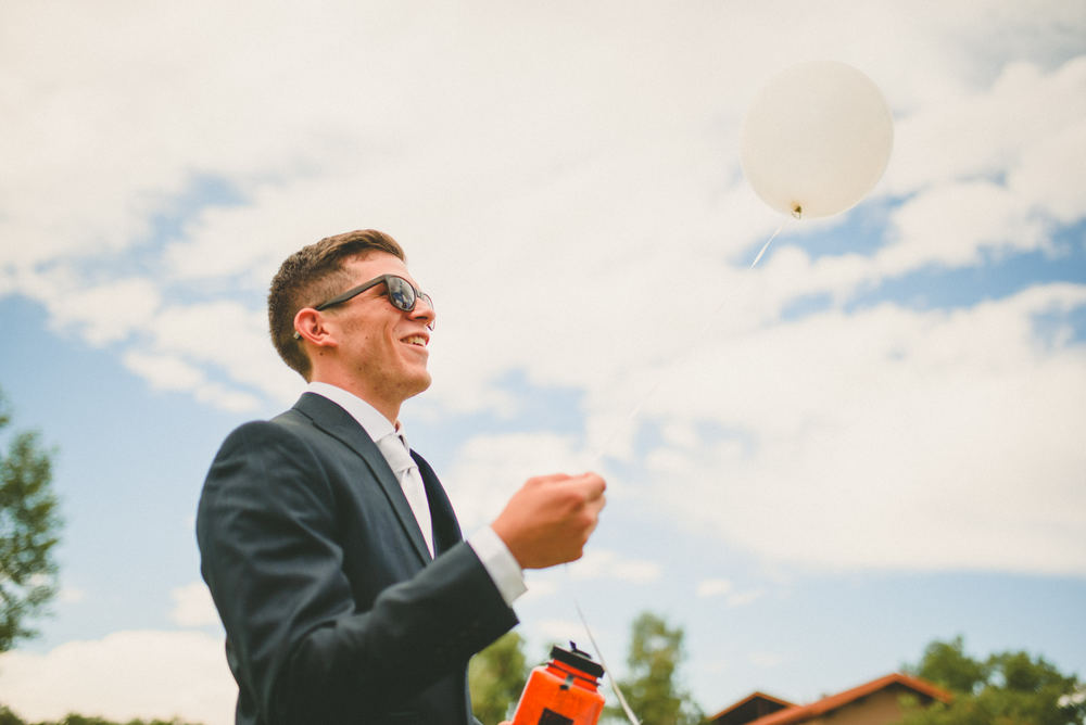 The groom is wearing a dark blue tuxedo and black sunglasses. He is smiling and holding a white balloon.