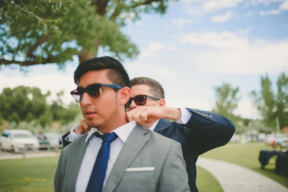 Groom standing behind and adjusting the collar of one of his groomsmen. They are both wearing sunglasses.