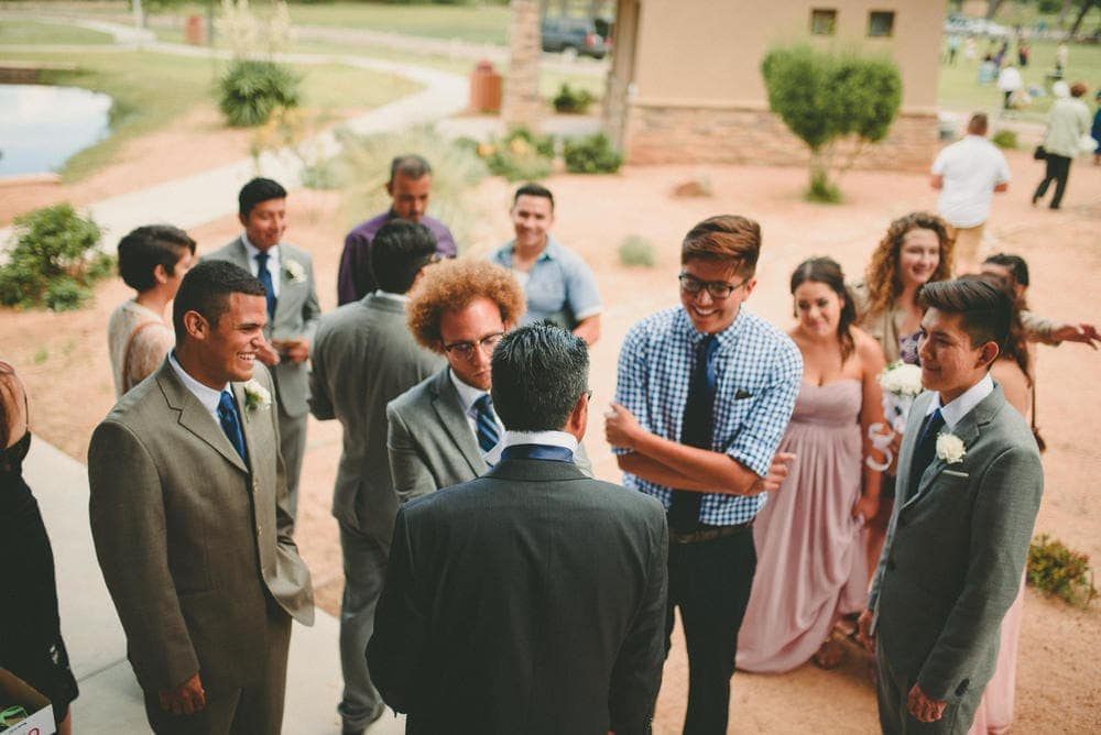 A group of groomsmen standing around watching as one of them helps the father of the bride tie his tie.