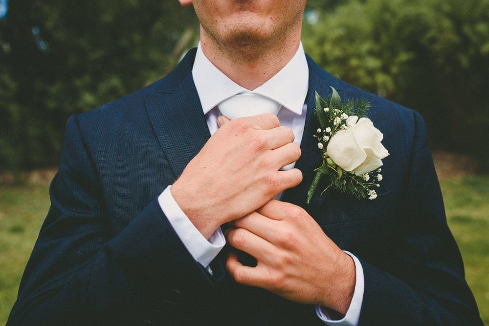 A close up view of the grooms hands as he adjusts his tie. He has a white flower on his left chest.