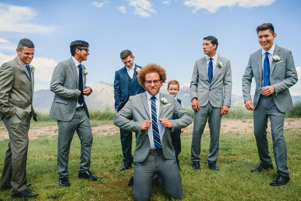 Several groomsmen and the ring bearer are gathered around one groomsmen who's on his knees in a GQ pose