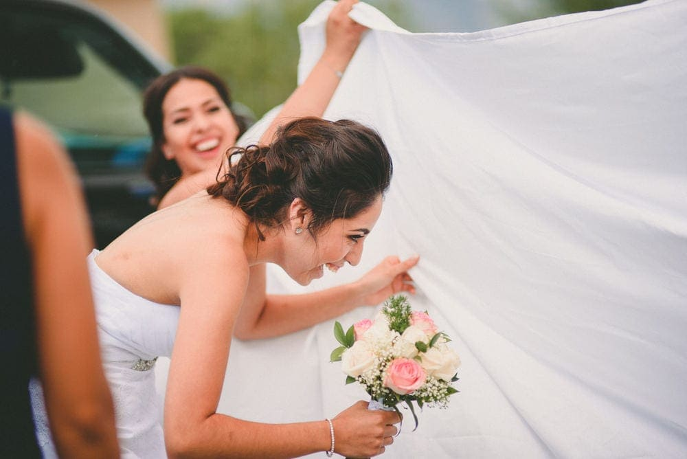 The bride is hiding behind a white sheet so her groom doesn't see her. The wind is blowing it around and everyone is laughing.
