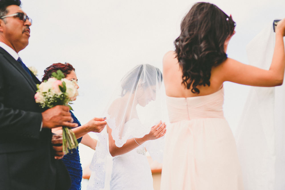 The bride is smiling and holding her vail with her hands so it won't blow away.