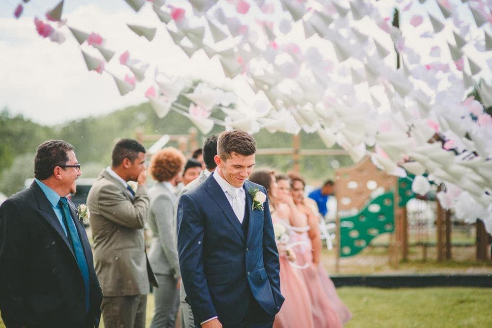 The groom is looking at the ground and smiling while he tries to avoid seeing his bride at Sandia Lakes Park