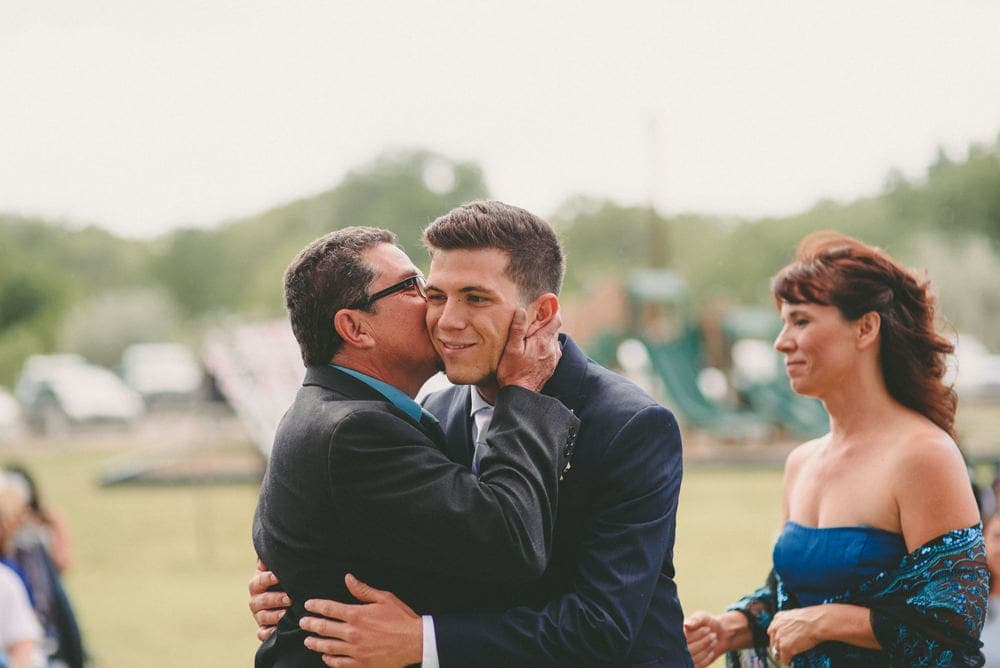 The father of the groom is holding the groom's face in his hands and kissing the groom on the cheek.