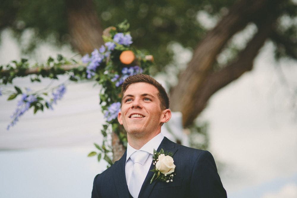 The groom is smiling as he sees his bride for the first time walking down the aisle for their wedding at Sandia Lakes Park.