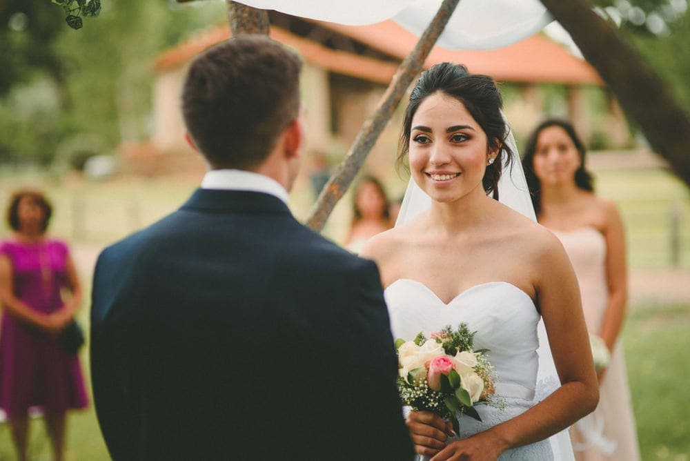 The bride is smiling at the groom as and holding her bouquet during their wedding at Sandia Lakes Park.