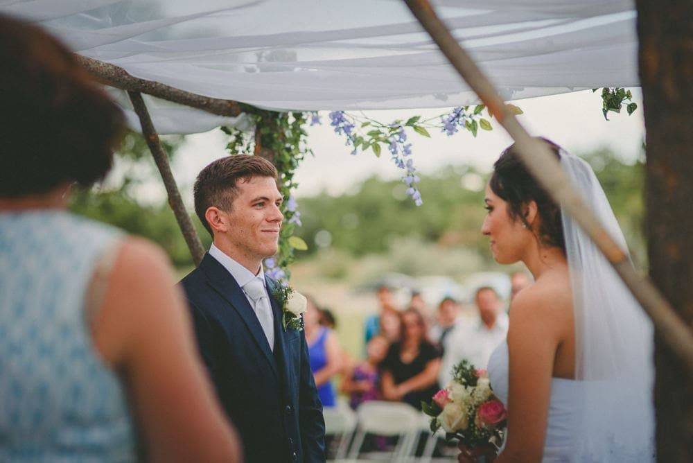 The groom is smiling at the bride as they stand under their arch for their wedding at Sandia Lakes Park.