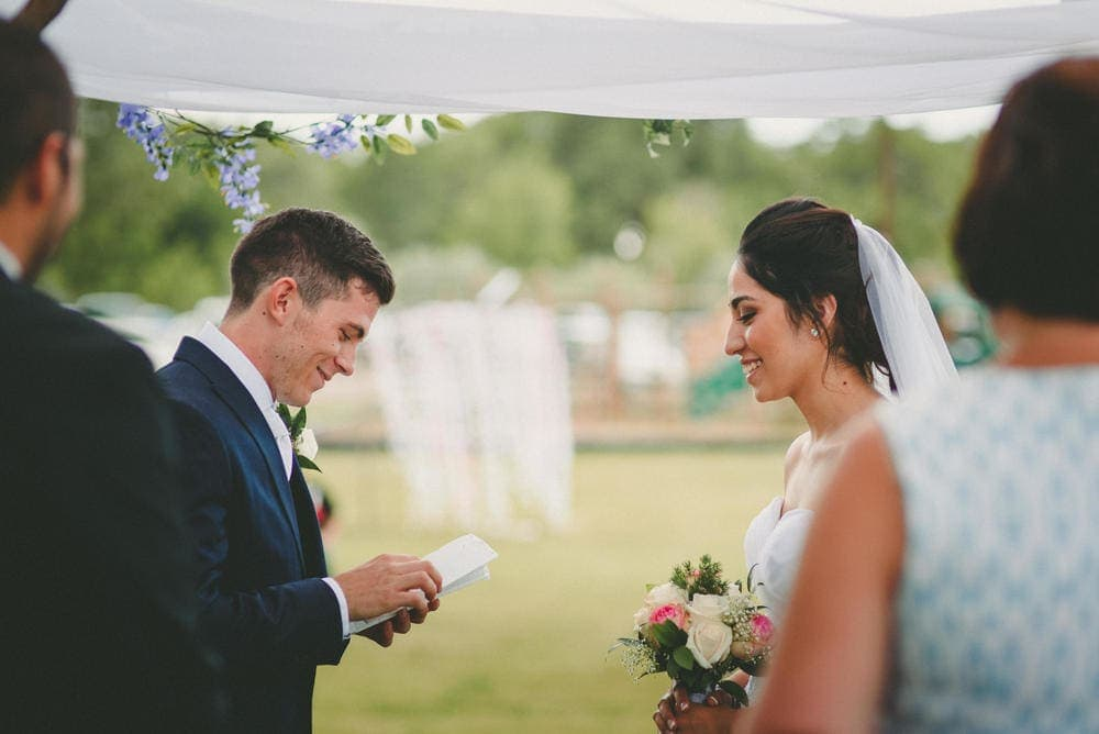 The groom is reading his notes before he says his vows. The bride is laughing at him.