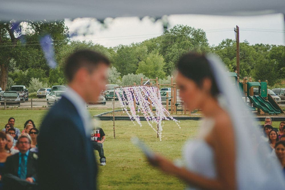 The bride and groom are in the foreground and blurred out. The background of their entryway is in focus.