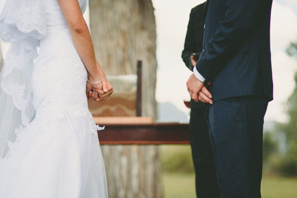 Close up view of the bride and grooms hands as they face each other during their wedding at Sandia Lakes Park.