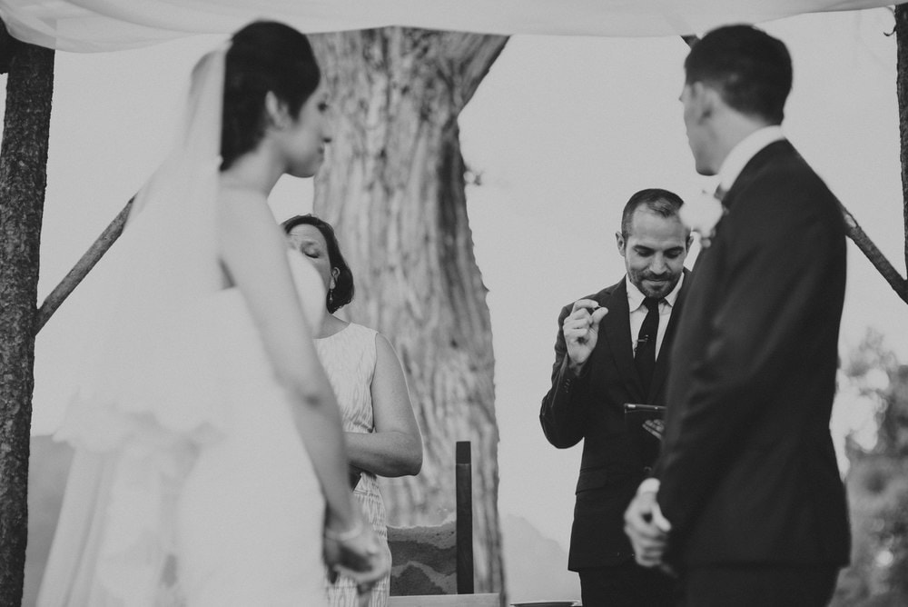 Black and white image of the minister in the background reading from the Bible as the bride and groom look at him.
