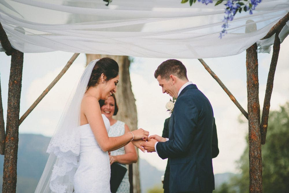 The groom is slipping the wedding ring onto the brides finger. They are both smiling and laughing.