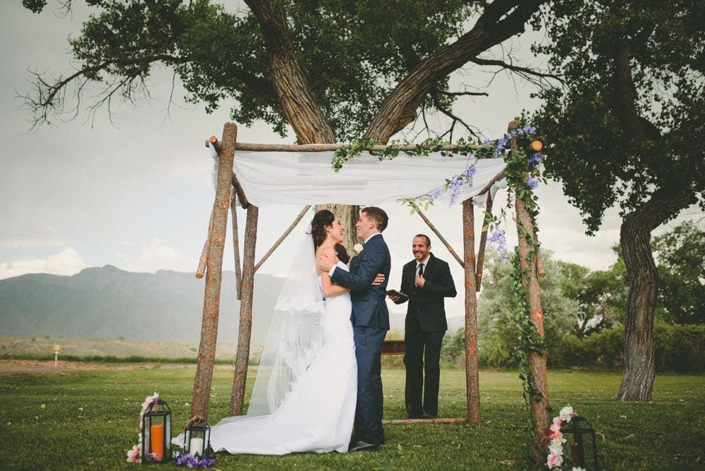 The bride and groom are embracing each other and laughing and smiling as they stand under their arch.