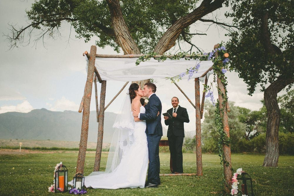 The groom is kissing his new bride as they stand under the arch at their wedding. The Sandia mountains can be seen in the background.