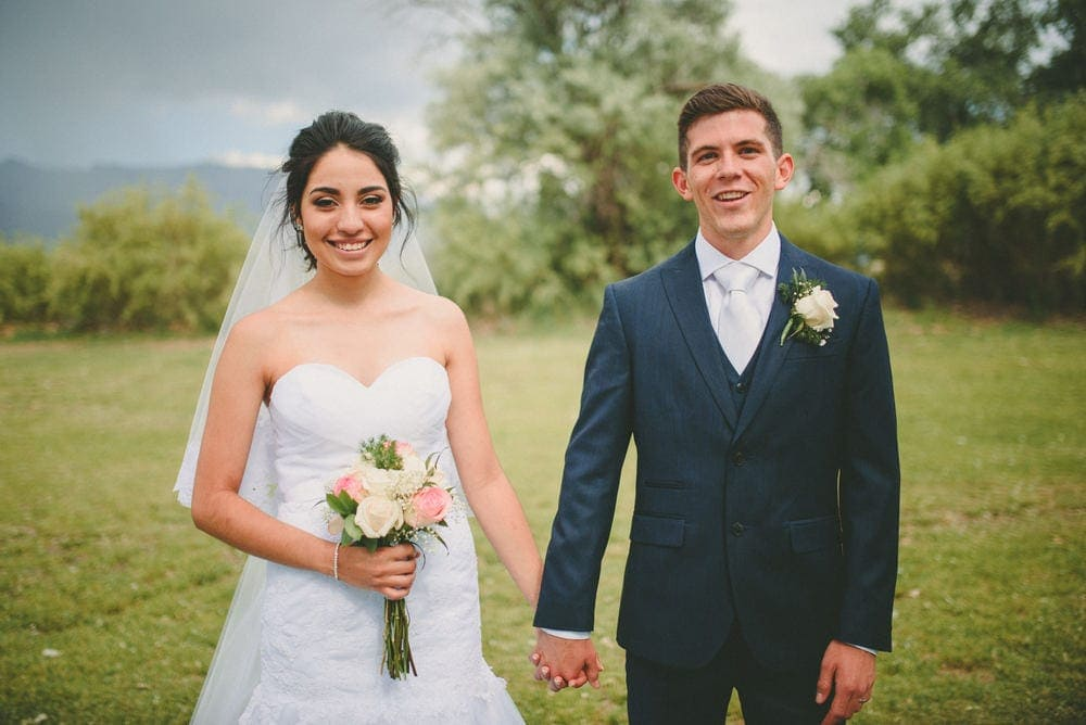 The bride and groom are holding hands and smiling. She is holding her bouquet.