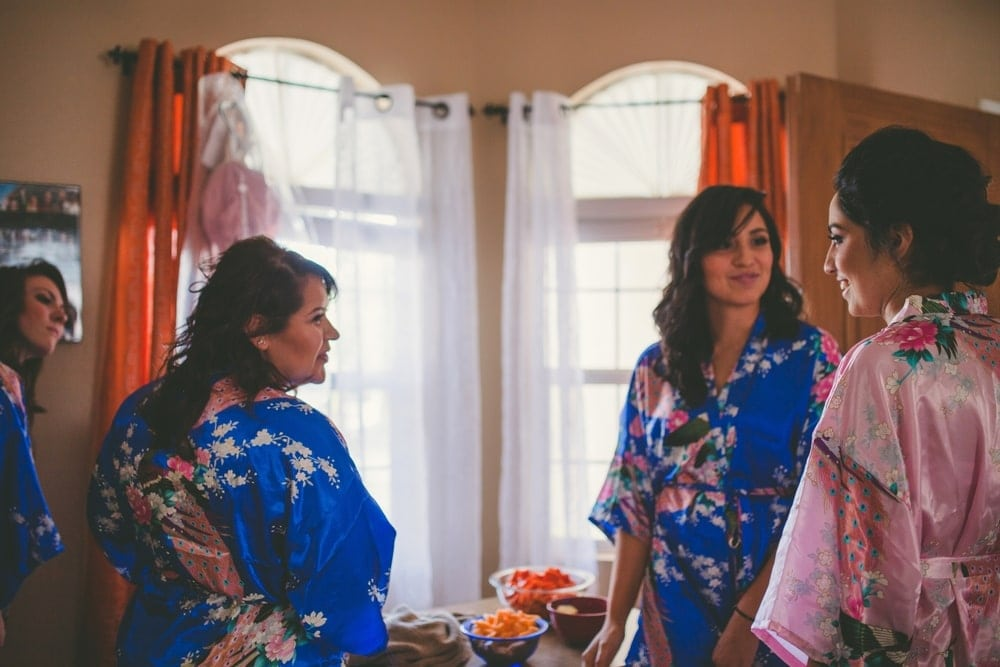 New Mexico bride wearing a pink robe and smiling at her bridesmaids while getting ready for her wedding. The bride's maids are wearing blue robes.