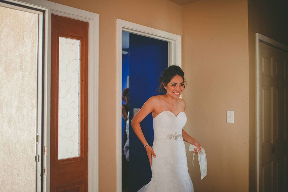 New Mexico bride trying on her dress for the first time. She has a big smile on her face.
