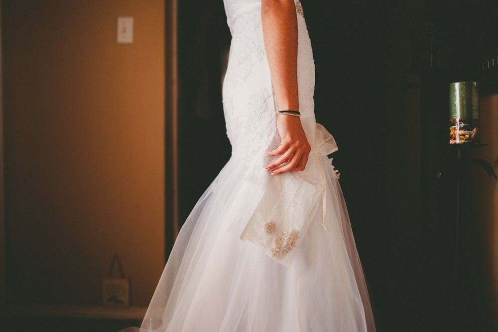 New Mexico bride's arm from the elbow down showing her hand holding a clear pouch with her jewellery in it.