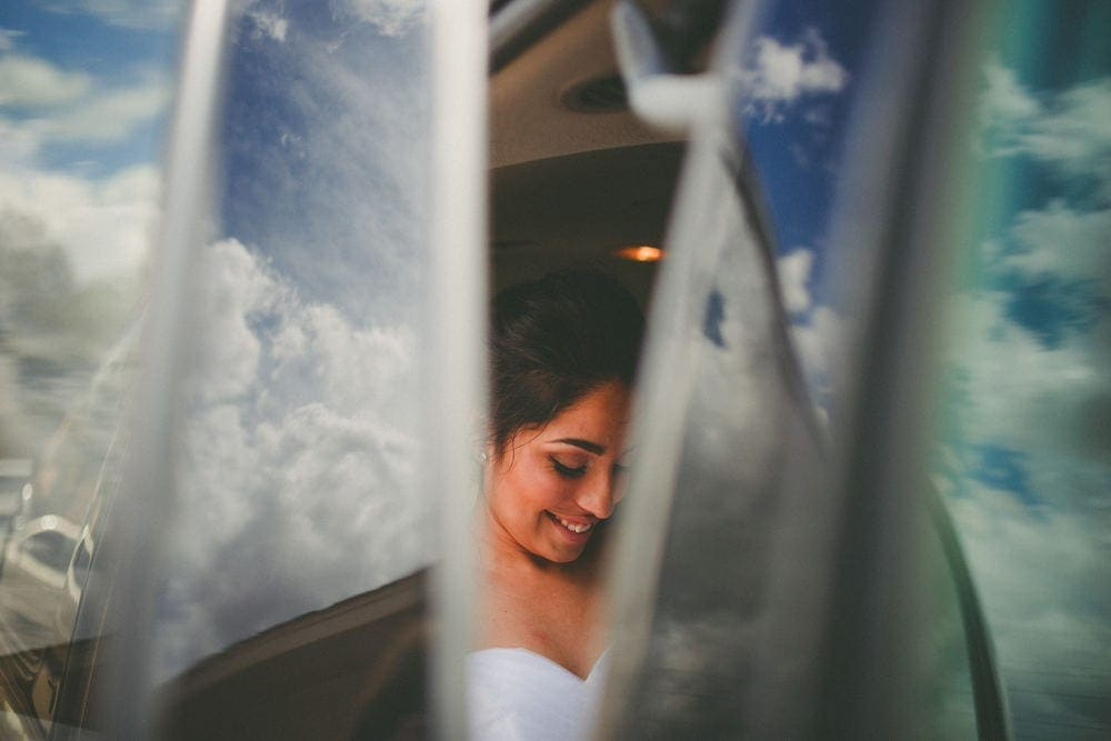 Bride getting into a vehicle to ride to her wedding location. She is smiling. A reflection of the clouds off the vehicle surrounds her face.
