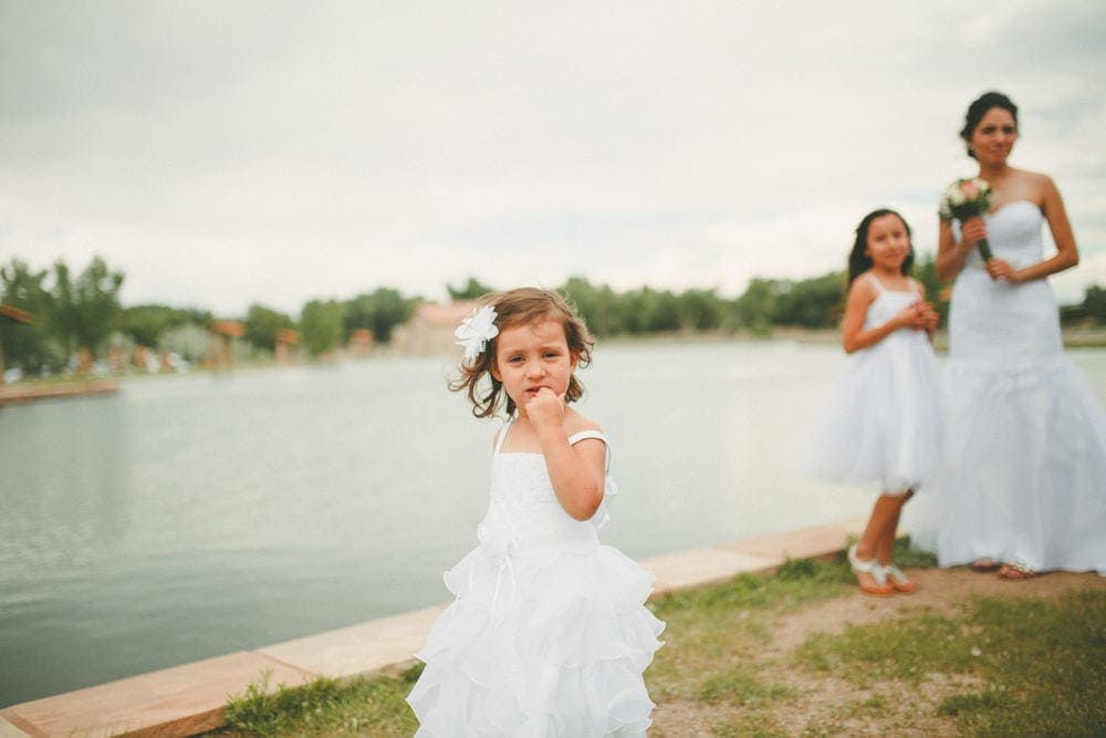 Flower girl standing in the foreground at Sandia Lakes Park. The bride can be seen standing in the background.