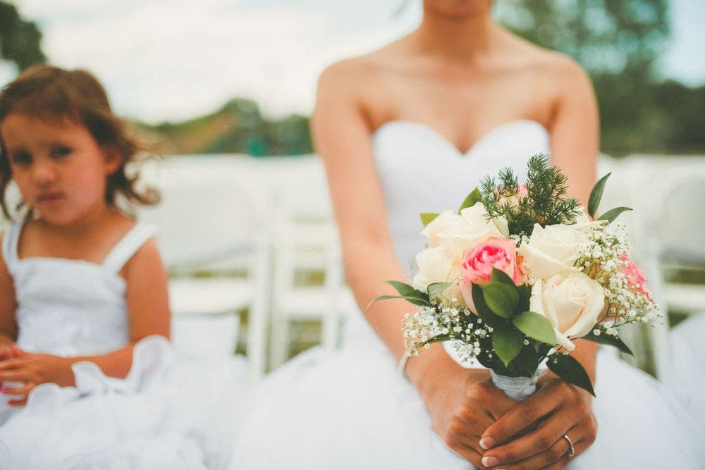 Close-up view of the bride's hands holding her bouquet. The flower girl is sitting next to the bride.