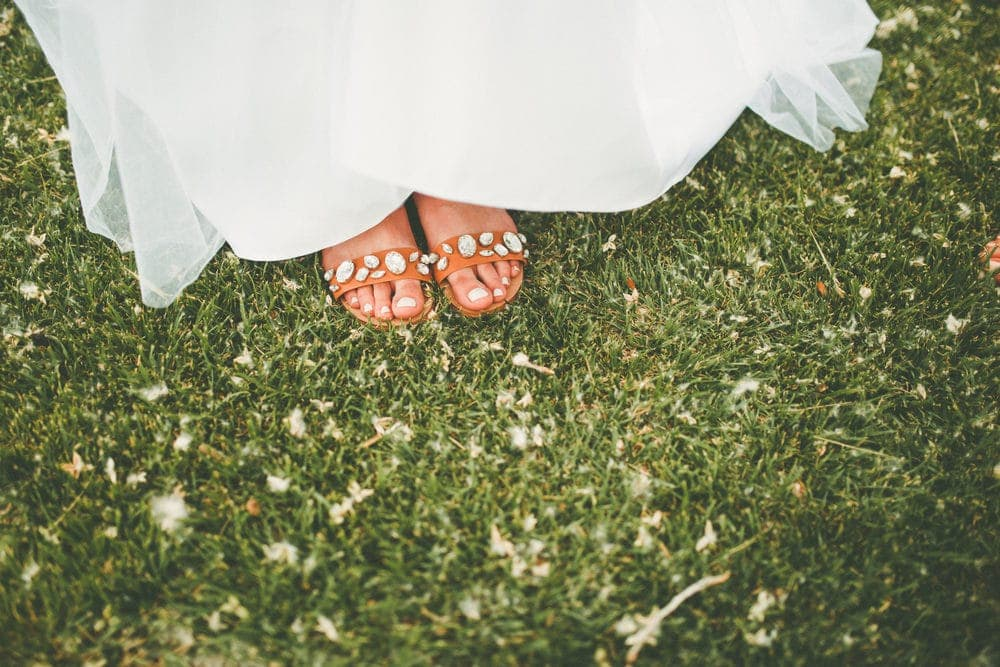 The brides sandals are shown with rhinestone straps standing on green grass.