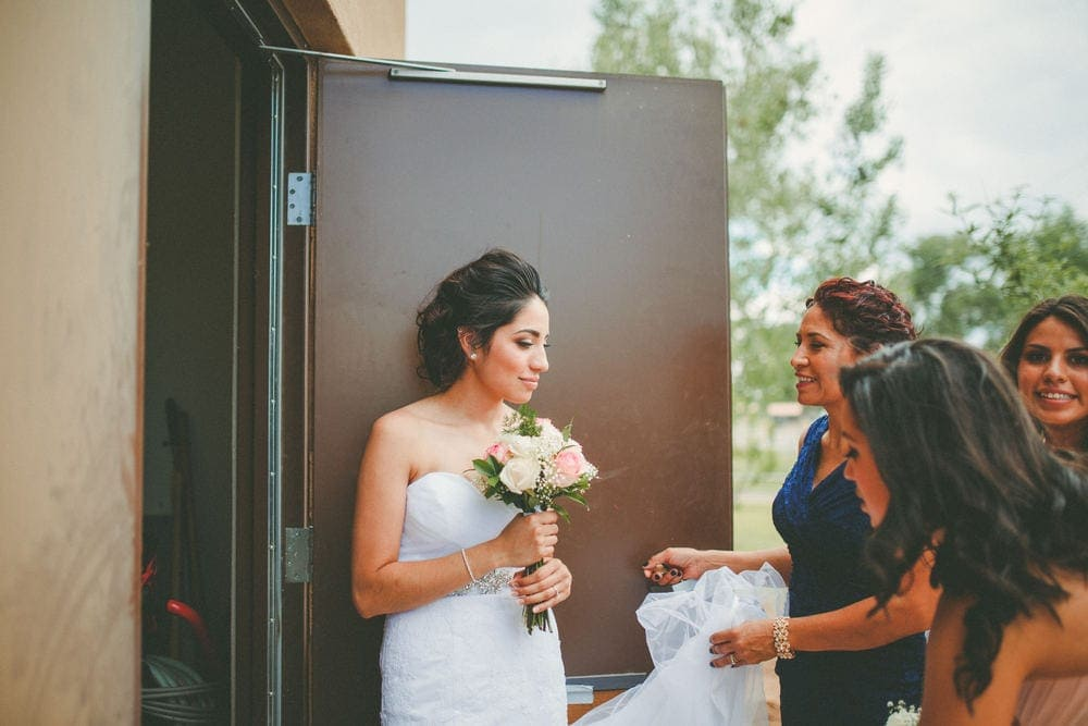 The bride smiling and laughing with her mother and sisters as they tend to her dress.