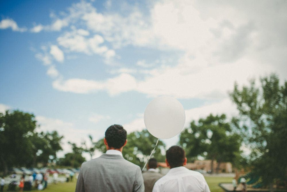 Two groomsmen walking toward the wedding ceremony away from the camera. The one on the left is holding a white balloon.