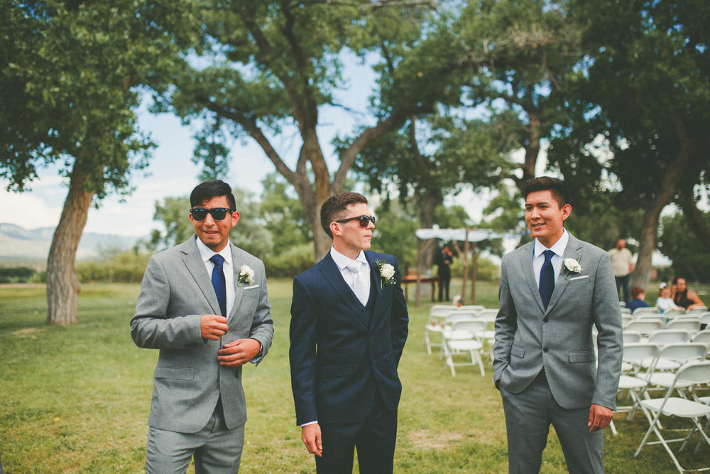 The groom is standing between two of his groomsmen. Two of them are wearing sunglasses. They look dapper.