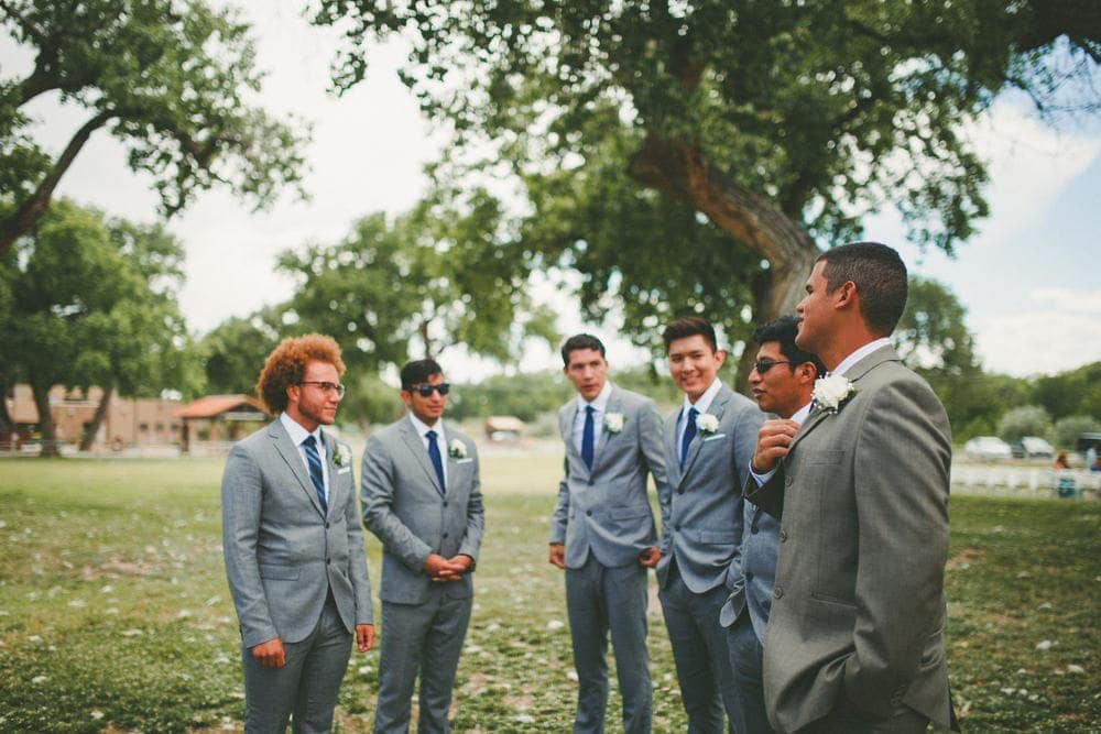 Six groomsmen standing together and joking with each other. They are wearing grey suits from H&M.
