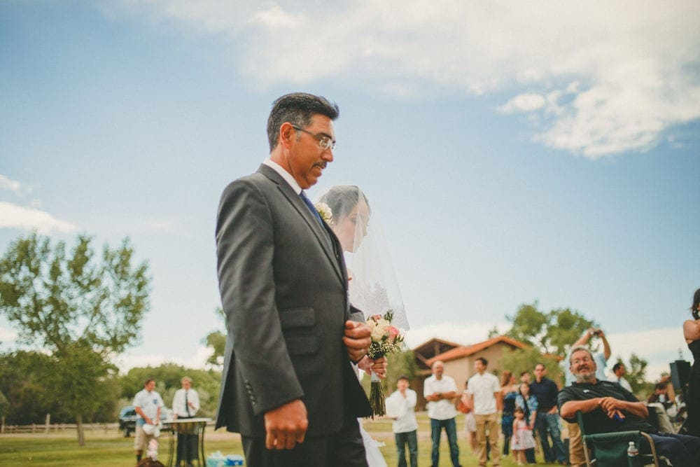 The father of the bride is walking the bride up the aisle at her wedding at Sandia Lakes Park.