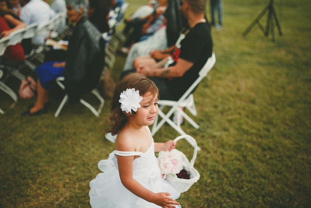 The flower girl is running down the aisle crying.