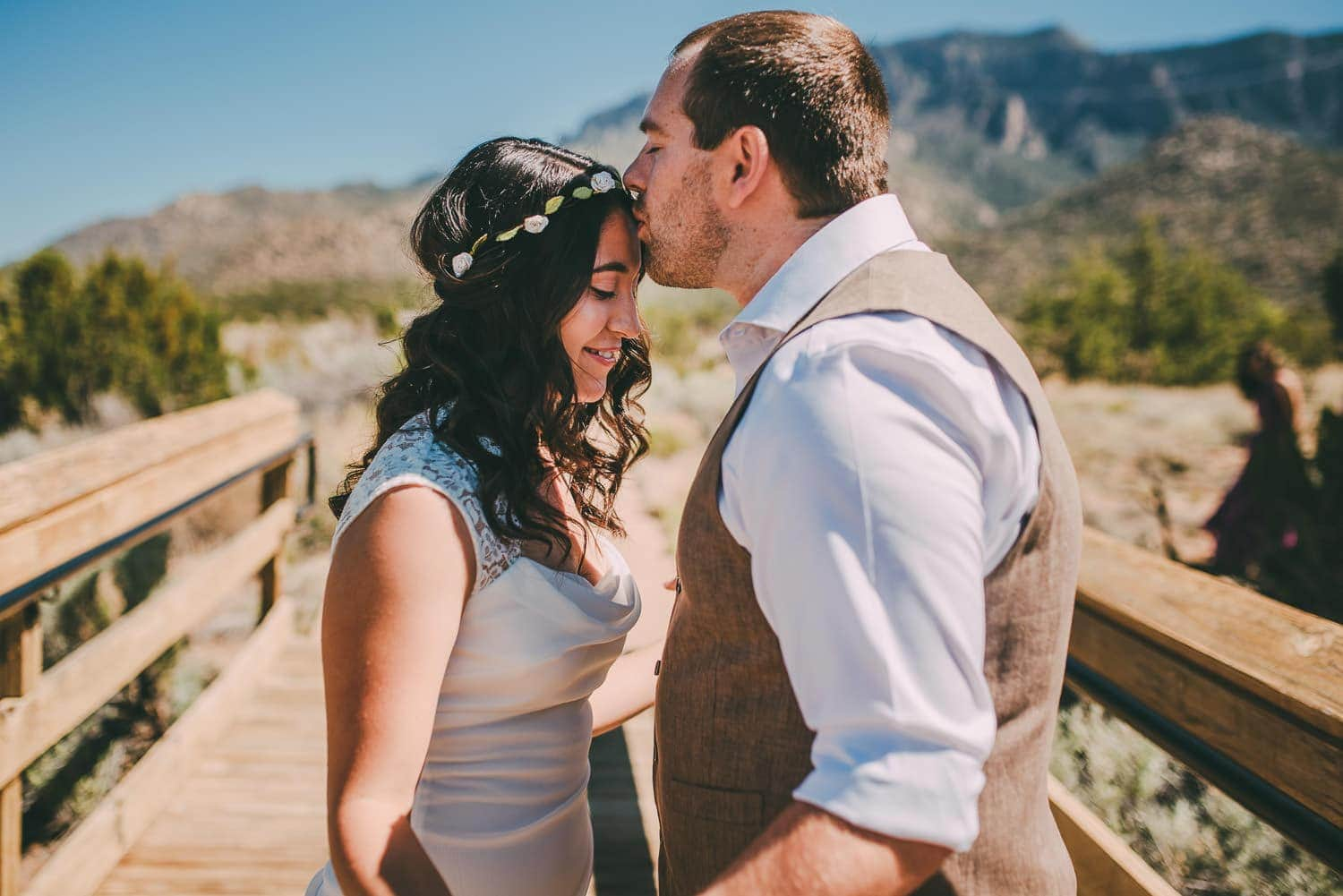A groom kissing his bride on her forehead. The Sandia mountains are in the background.