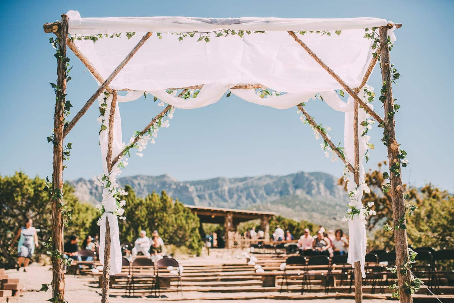 The wedding arch is in the foreground and the blue sky and sandia mountains are in the background