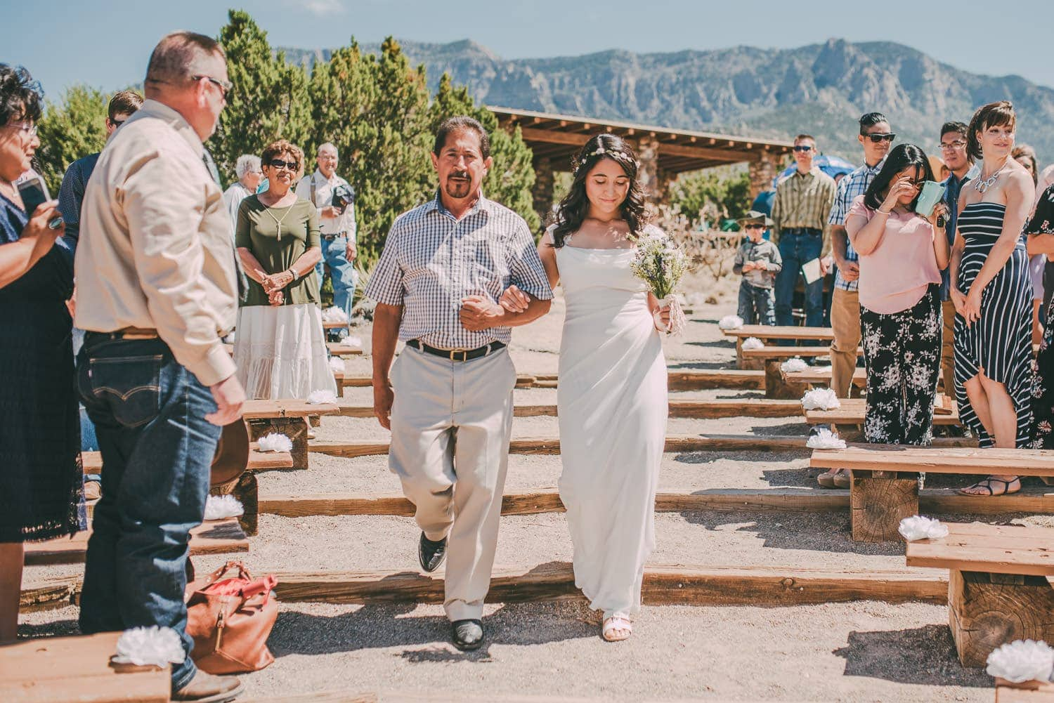 Father of the bride escorting her down the aisle. The Sandia Mountains are seen in the background.