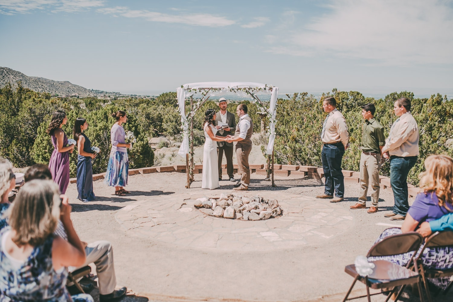 Wide view of the wedding party during the ceremony. Albuquerque can be seen in the background.