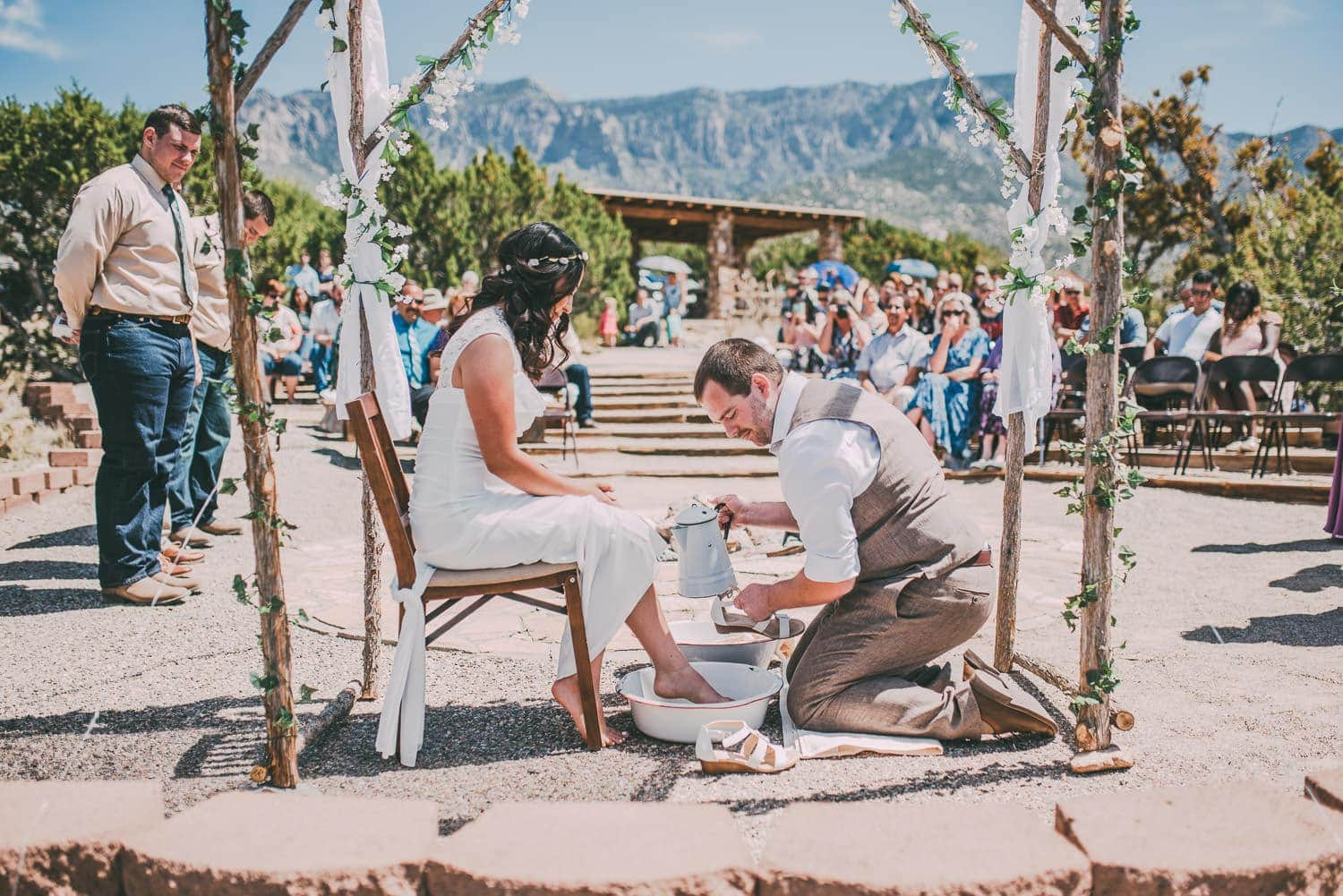 The groom is washing the brides feet. The mountains can be seen in the background.
