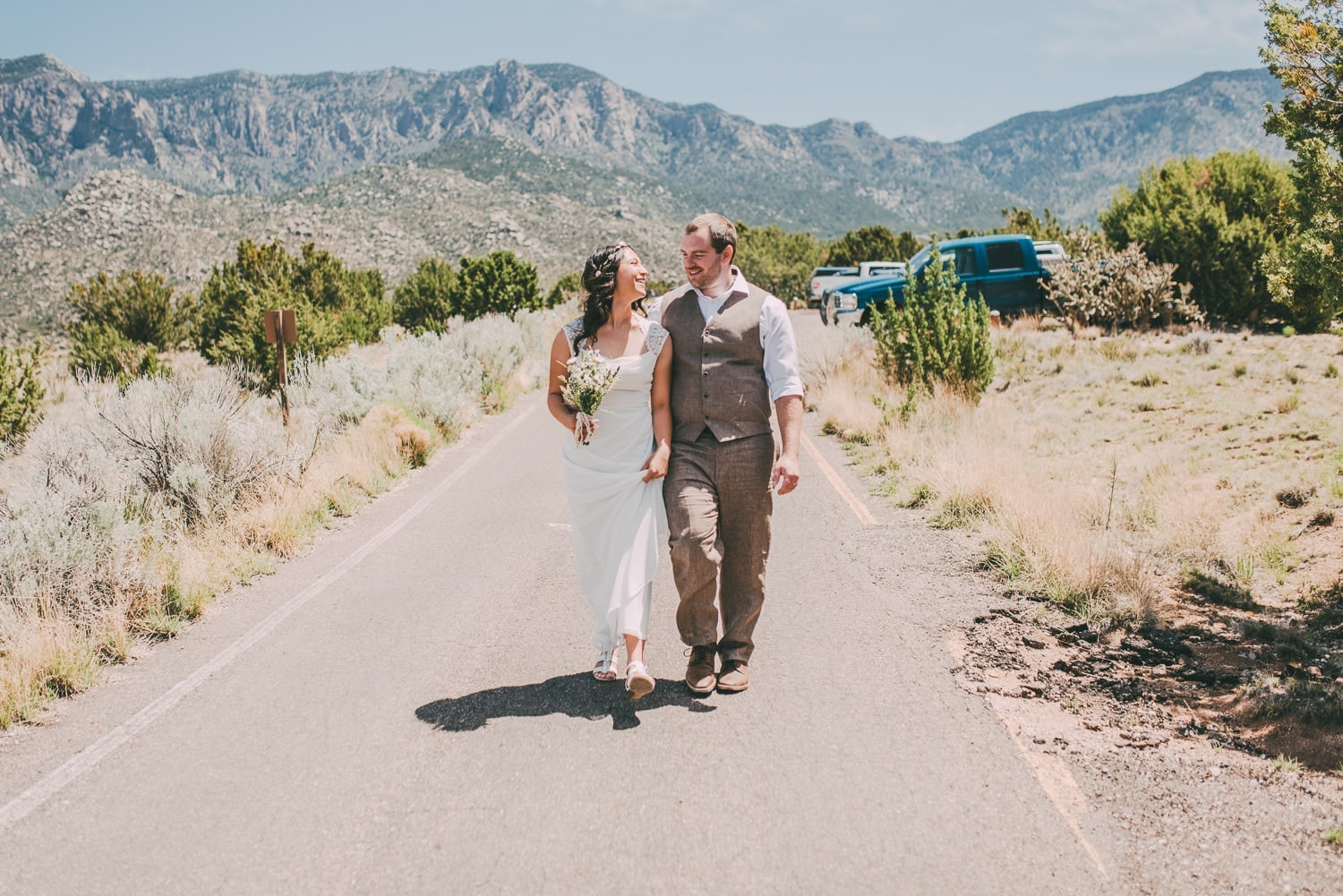 The new husband and wife are walking to their reception following their wedding. The Sandia mountains are seen in the background.