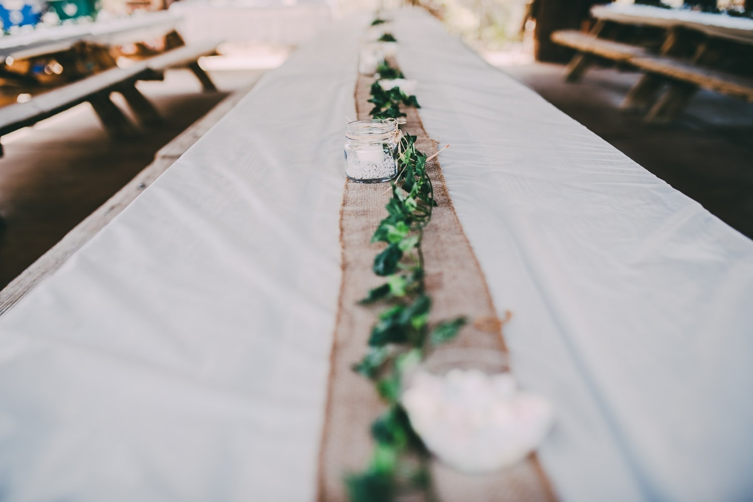 A table runner with green leaves and candles running down the center