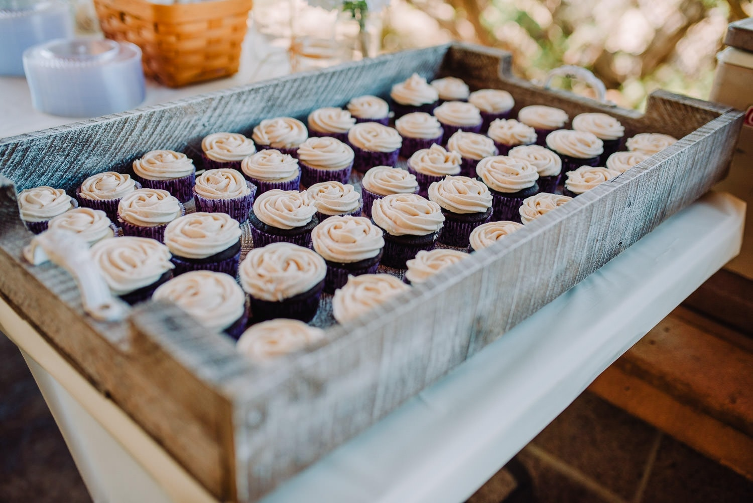 A close view of purple cupcakes with white frosting at the wedding reception at Elena Gallegos Park