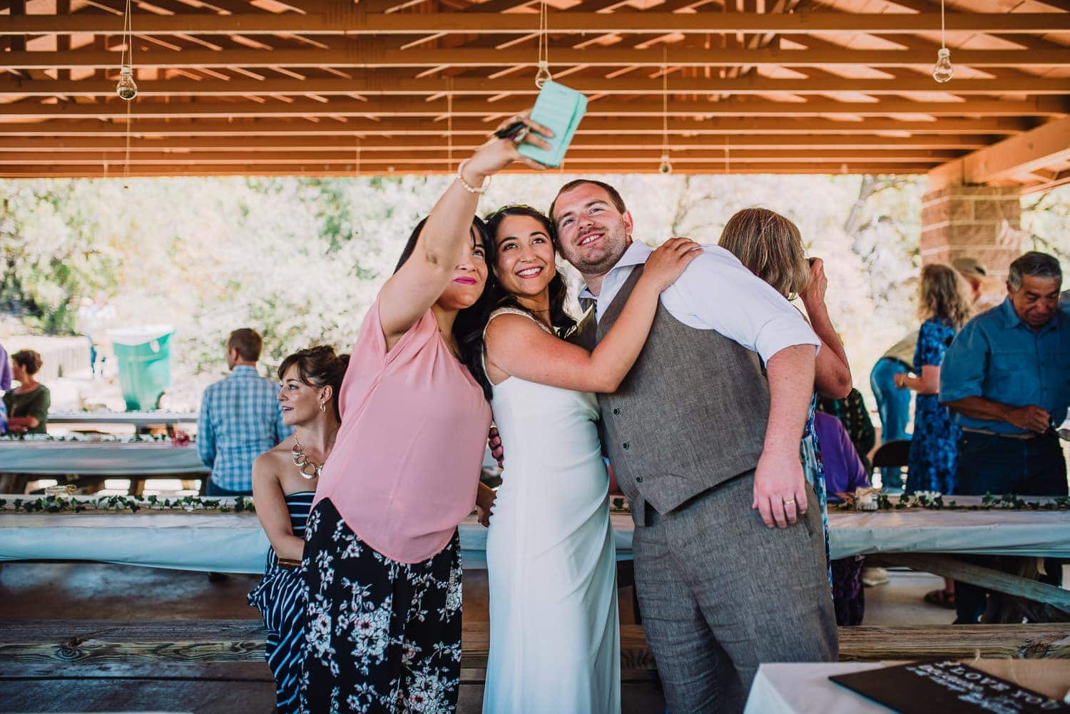 The bride and groom are smiling for a selfie with a friend.