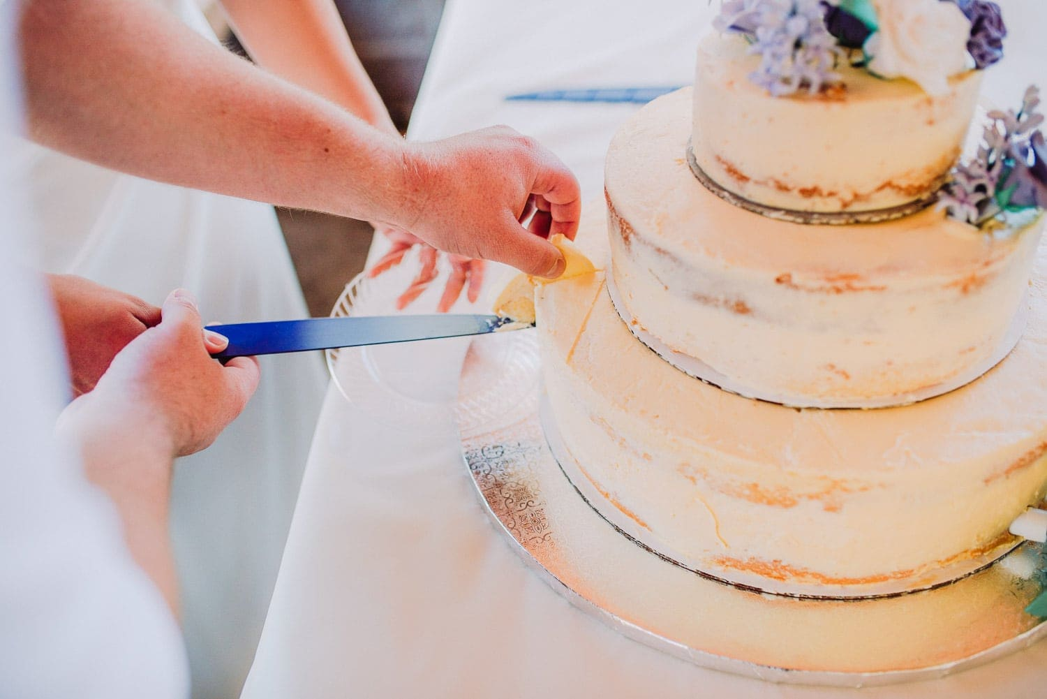 The bride and groom are cutting their wedding cake.