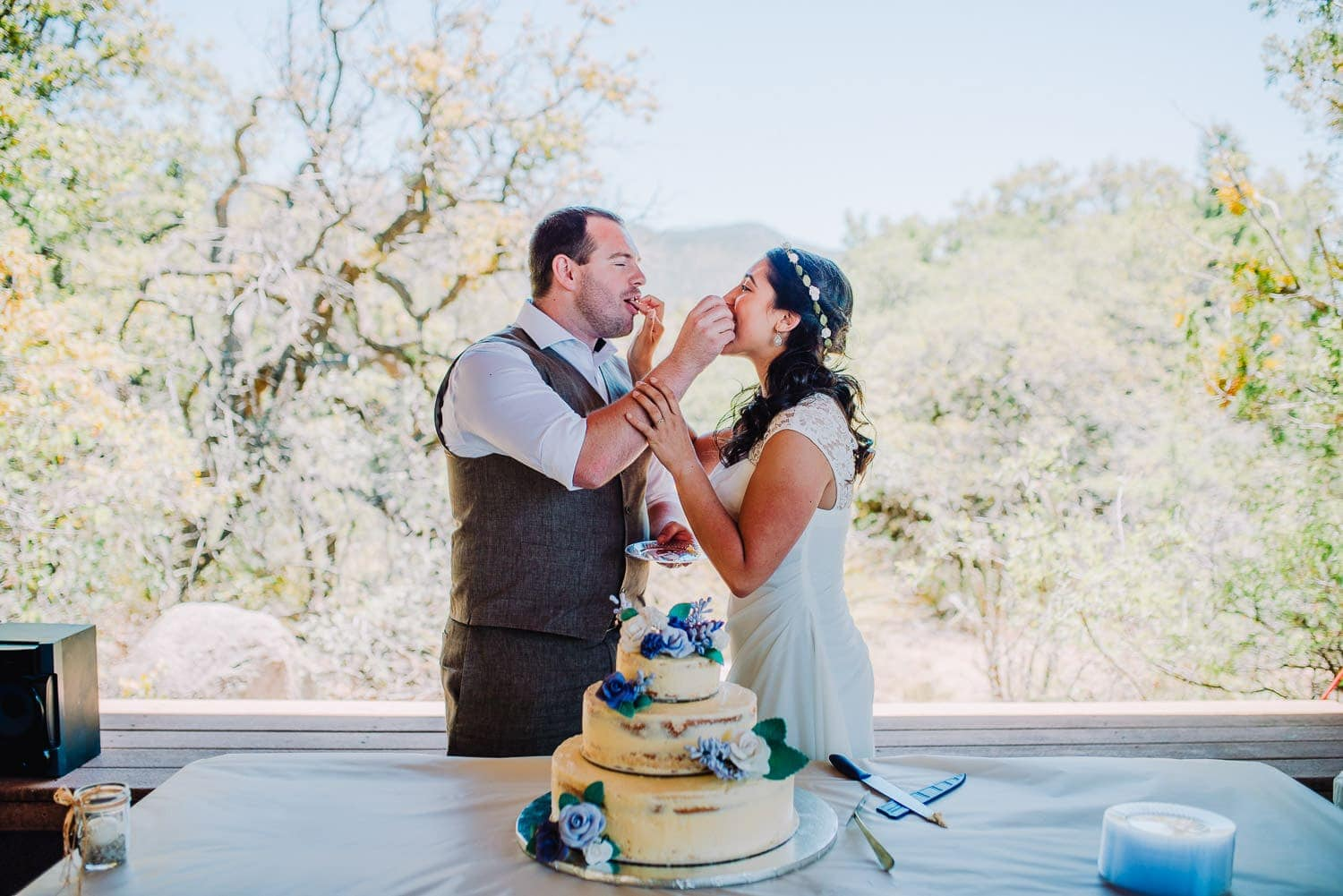 The bride and groom are feeding each other a piece of cake and smiling.