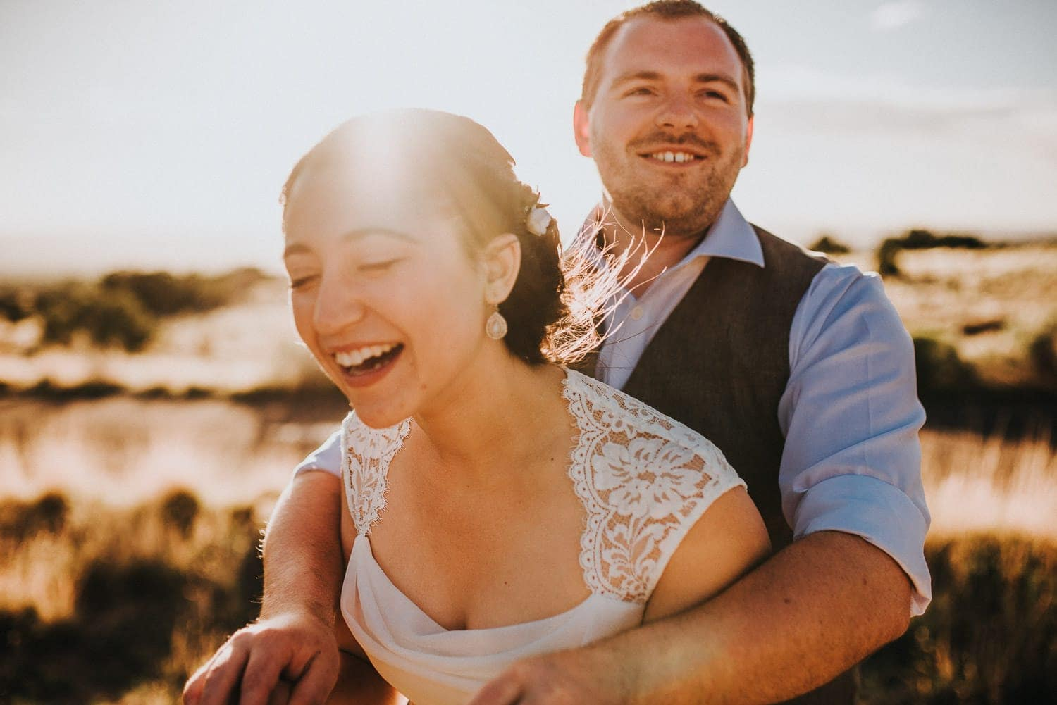 The bride is laughing hysterically as the groom hold her and smiles.